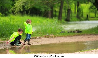 Happy Kids Throwing Stones Into Puddle - Happy cute siblings...
