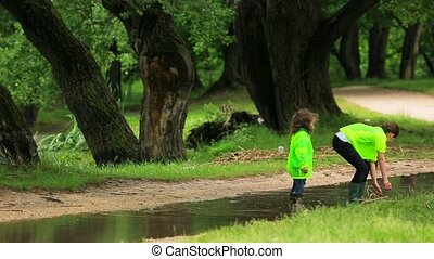 Two Children Walking In Puddle In Park - Two children - boy...