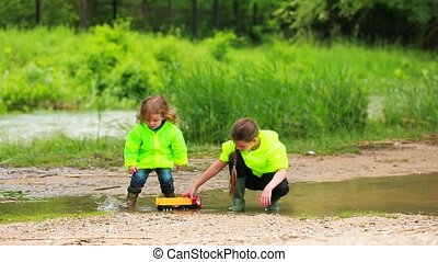 Happy Children Playing In Puddle At Green Meadow - In the...