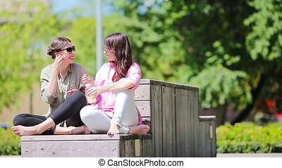 Happy young urban girls listening music in park outdoor...