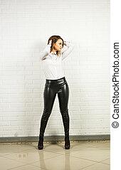 Woman wearing black leather pants indoors - Woman wearing...