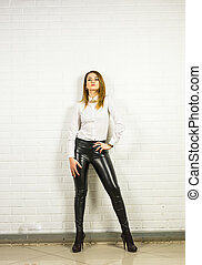 Woman wearing black leather pants and high heel shoes indoors