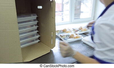 An employee of airline catering facility puts trays of food...