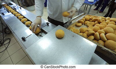 Worker puts freshly baked rolls on conveyor for hermetic...