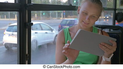 Woman using tablet in bus - Smiling young woman sitting in...