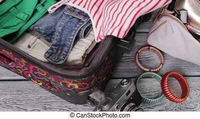 Camera near suitcase with clothes. American dollars in...