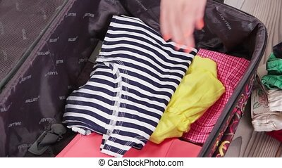 Hands put clothes into suitcase. Open suitcase with summer...