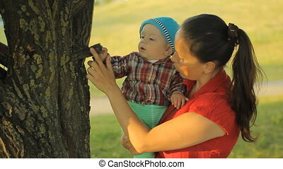 Mother is standing in the park near the trees and holding her smiling little baby boy son. Kid touch tree