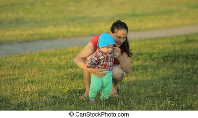 Mom playing with baby son in the park. The child makes the first steps