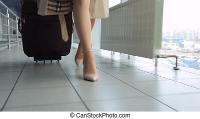 Woman in heels goes at airport and roll suitcase on wheels....