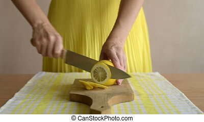 Woman slicing a lemon on a shabby wooden board.