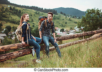 A couple of tourists sitting on a wooden fence and view...