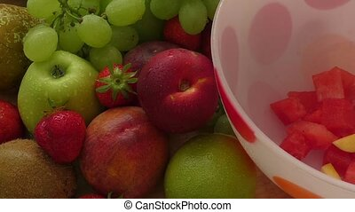 Fruit salad in a bowl with strawberries, kiwi, peach and...