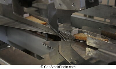 Automatic packaging of bread in plastic on a conveyor belt...