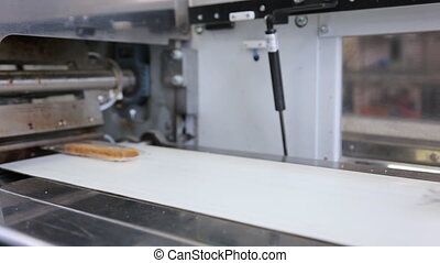 On conveyor pieces of bread packed in transparent packaging....