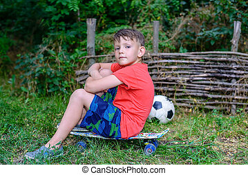 Confident jaunty young boy sitting on a skateboard with...