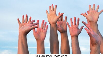 People raising hands up - Several people raising hands up in...