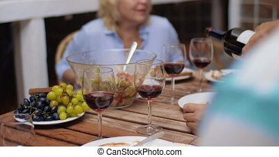 Man pouring red wine during the dinner - Late family dinner...