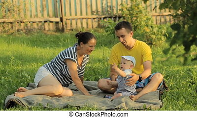 Happy family of three lying in the grass in summer park. They play and smile