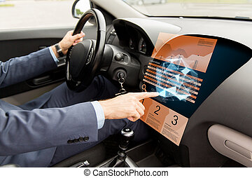 man driving car and pointing to on-board computer -...