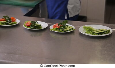 A worker puts slices of vegetables on plate closeup. A...