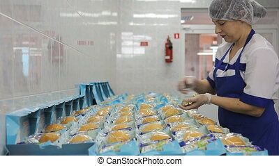 In airport factory the woman is packing the food in lunch boxes