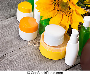 Different natural body care cosmetic products and sunflowers