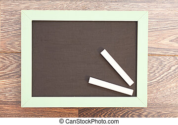 school wooden blank blackboard and white chalks on wooden...