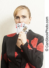 Pretty young woman holding playing cards against wallpaper background