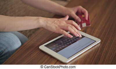 Woman's hands typing security code from credit card - Young...