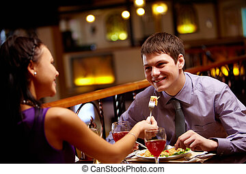 With love - Woman spoon-feeds her boyfriend in the...