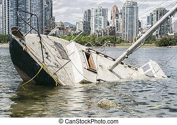 Shipwreck in front of a city - Sinking sailboat abandoned on...