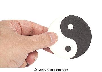 Hand Holding Yin-Yang Symbol isolated on white