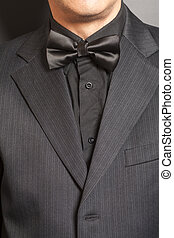 Man wearing a black suit and bow tie