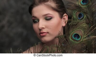 model blowing on the peacock feather - Beautiful girl with...