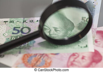 Yuan chinese money with magnifier glass isolated on gray