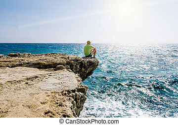 A man sits on a ledge of rock above the sea at Cape Greco .