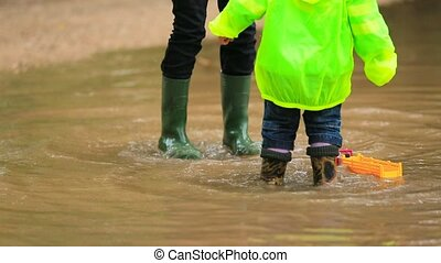 Happy Children Jumping In Huge Puddle - Wait down shot of...