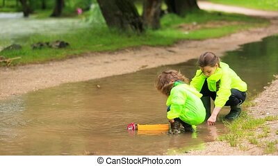 Adorable Kids Playing In Huge Puddle After Rain - In the...
