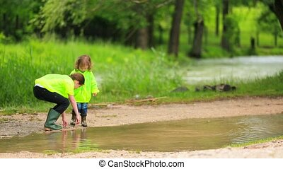 Children Throwing Stones Into Puddle In Park - Two cute...