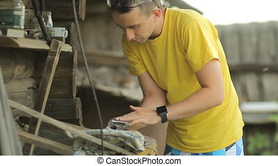 Young man squeezes a metal part in a vise. Against the backdrop of a country house building