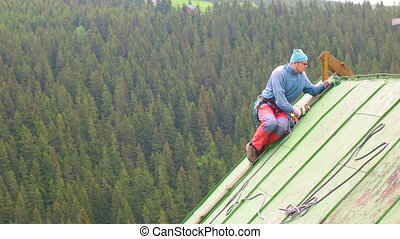 Man Working on the Roof, Checking Safety Gear - Adult...