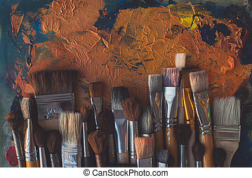 Paintbrush collection on old palette top view. Mixing...