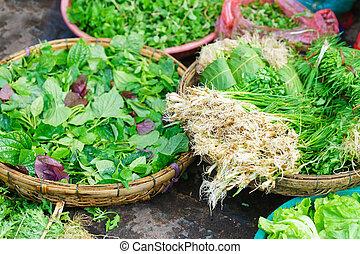 Asian street market selling fresh leaves of garden stuff -...