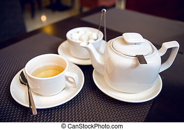 white teapot with tea Cup, saucer and teaspoon