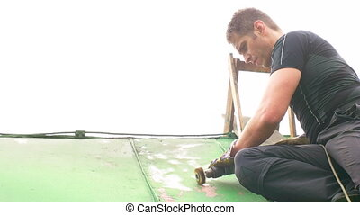 Man Working on the Roof, Sandering Paint - Adult caucasian...