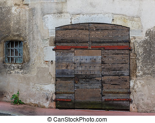 Facade of an old building with wooden gate and with a broken...