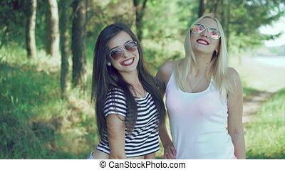 Two pretty girls with claret lips posing to camera in the park. 4k