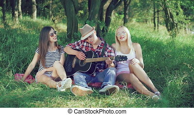 Happy friends playing the guitar and smiling on the grass in...