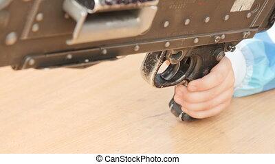 Kids hand touches a machine gun. - Child hands on a machine...